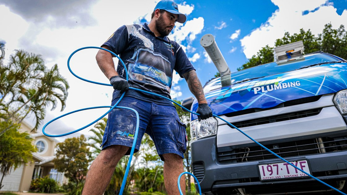 Brisbane plumber unblocking a drain with a water jetter